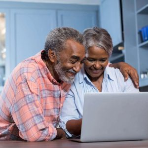 A senior couple sitting together at a counter looking at a laptop